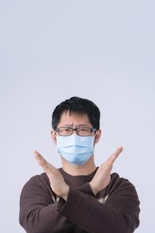 Portret van een jonge aziatische man, die nee zegt tegen een coronavirusinfectie met het dragen van een medisch chirurgisch blauw gezichtsmasker geïsoleerd op een witte achtergrond, close-up, close-up.