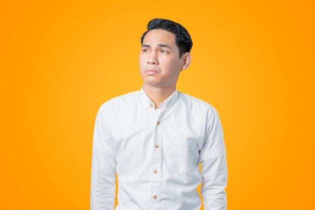 Portret van een jonge aziatische man die opkijkt met verveelde uitdrukking