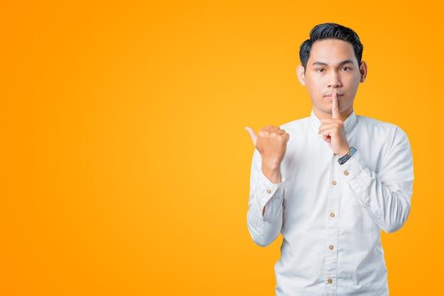 Portret van een jonge aziatische man die vraagt om stil te zijn en wijst om ruimte te kopiëren