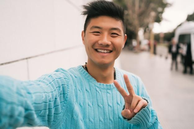 Portret van een jonge aziatische man die zelfverzekerd kijkt en een selfie neemt terwijl hij buiten in de straat staat.