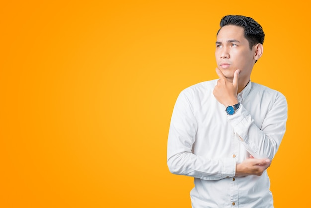 Portret van een jonge aziatische man die zijwaarts denkt en kijkt