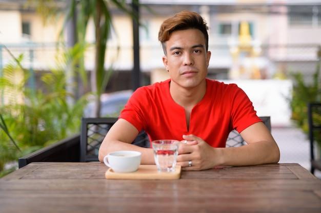 Portret van een jonge aziatische man in de coffeeshop buitenshuis
