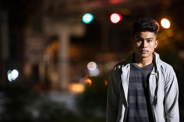 Portret van een jonge aziatische man in de stad straat 's nachts buiten