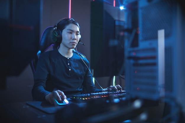 Portret van een jonge aziatische man met behulp van computer in donkere cyber interieur, kopieer ruimte