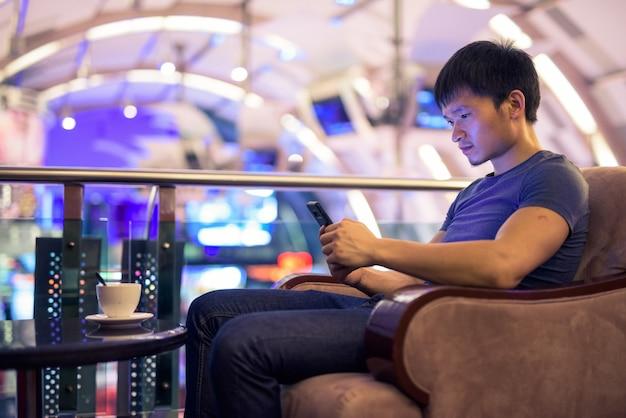 Portret van een jonge aziatische man met behulp van telefoon en zit in het winkelcentrum