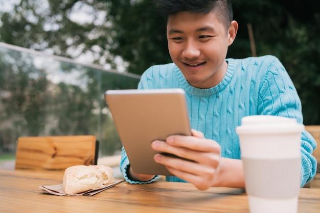 Portret van een jonge aziatische man met behulp van zijn digitale tablet zittend in een coffeeshop. technologie concept.
