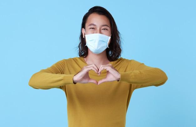Portret van een jonge aziatische man met een gezichtsmasker dat beschermt tegen het corovavirus geïsoleerd op een blauwe studioachtergrond.