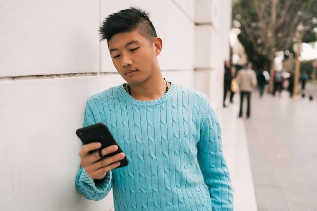 Portret van een jonge aziatische man met zijn mobiele telefoon die zich buiten in de straat bevindt. communicatie concept.
