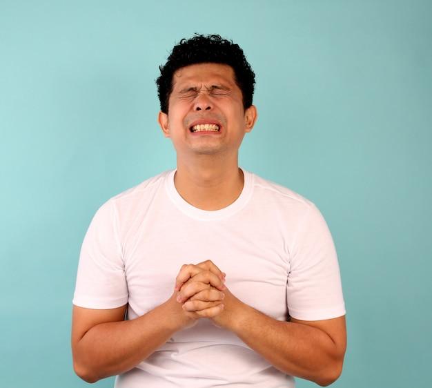 Portret van een jonge aziatische man teleurgesteld, gericht op mannen in witte t-shirts op een blauw.