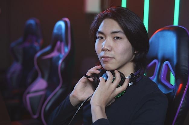 Portret van een jonge aziatische man tijdens het spelen van videogames in pro-gaming studio, kopie ruimte