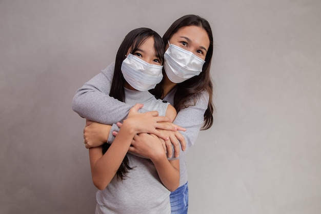 Portret van een jonge aziatische moeder met haar kinddochter die een masker draagt. moeder en dochter dragen masker om covid 19 te beschermen, quarantaine. blijf thuis concept.