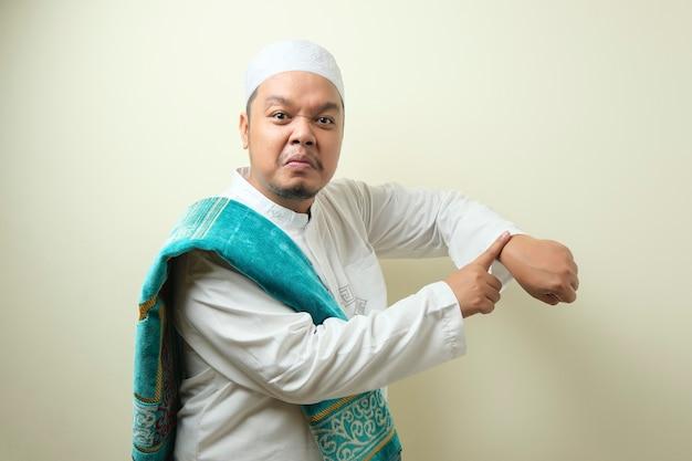 Portret van een jonge aziatische moslimman die op zijn polshorloge wijst, baas die waarschuwt voor tijdconcept. de man ziet er gek uit tegen de ivoren muur