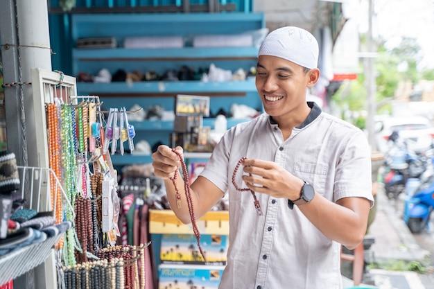 Portret van een jonge aziatische moslimmens die voor islamitische parels winkelt