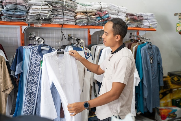 Portret van een jonge aziatische moslimmens die voor kleren bij opslag winkelt