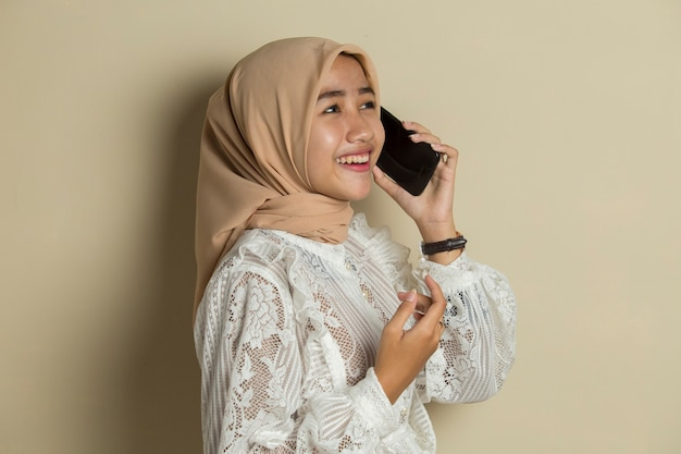 Portret van een jonge aziatische moslimvrouw die mobiele telefoon met behulp van