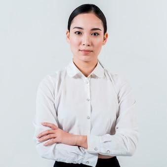 Portret van een jonge aziatische onderneemster met haar gekruiste die wapen het kijken aan camera op witte achtergrond wordt geïsoleerd