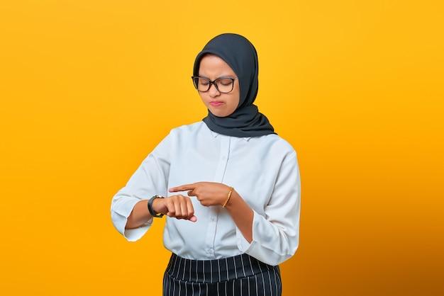 Portret van een jonge aziatische vrouw die de tijd controleert op het horloge dat over gele achtergrond wordt geïsoleerd