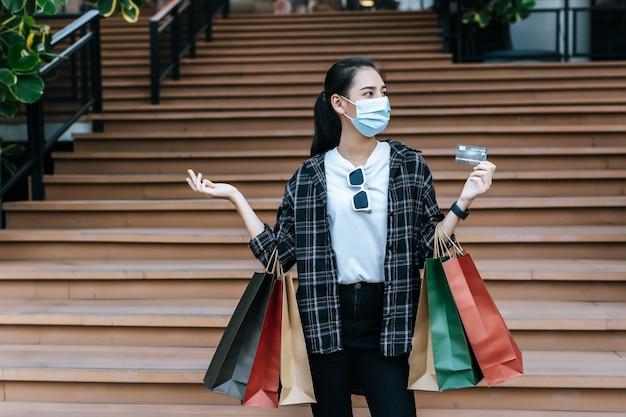 Portret van een jonge aziatische vrouw die een beschermingsmasker draagt dat op de trap zit met een papieren boodschappentas