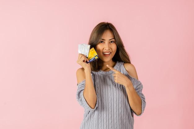 Portret van een jonge aziatische vrouw die een creditcard houdt zij denkt aan winkelen