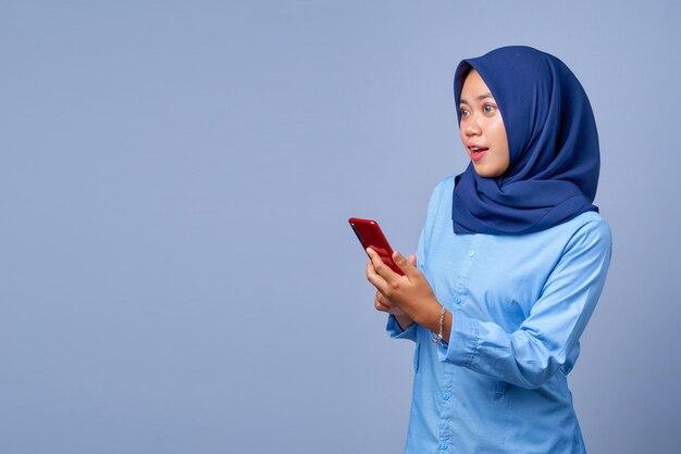 Portret van een jonge aziatische vrouw die een smartphone vasthoudt en zijwaarts kijkt met een geschokte uitdrukking