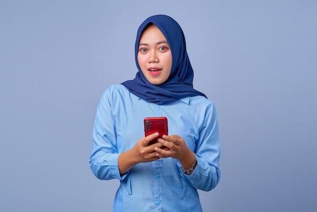 Portret van een jonge aziatische vrouw die een smartphone vasthoudt met een geschokte uitdrukking en een hijab draagt