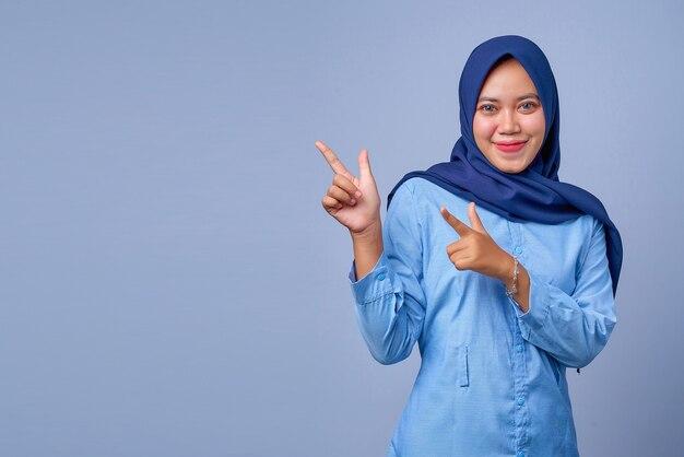 Portret van een jonge aziatische vrouw die lacht en wijst om de ruimte te kopiëren