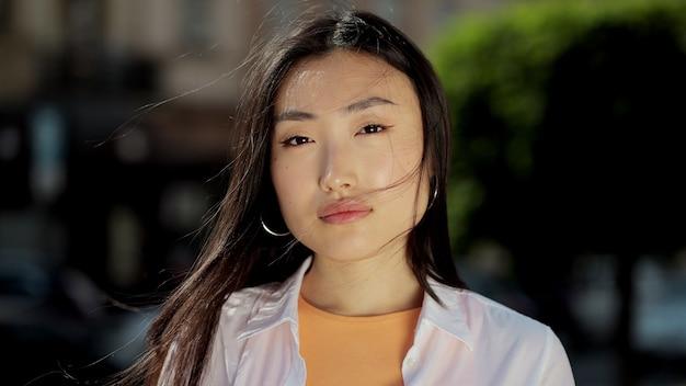 Portret van een jonge aziatische vrouw in terloops gekleed op zoek naar camera buiten op straat close-up gezicht van mooi aziatisch meisje staan in de straten van de stad zomer mooie dame portret gelukkig buiten