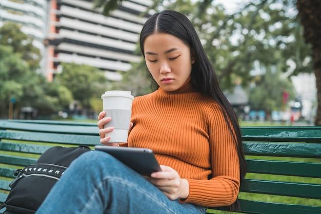 Portret van een jonge aziatische vrouw met behulp van haar digitale tablet terwijl ze een kopje koffie in het park buiten houdt.
