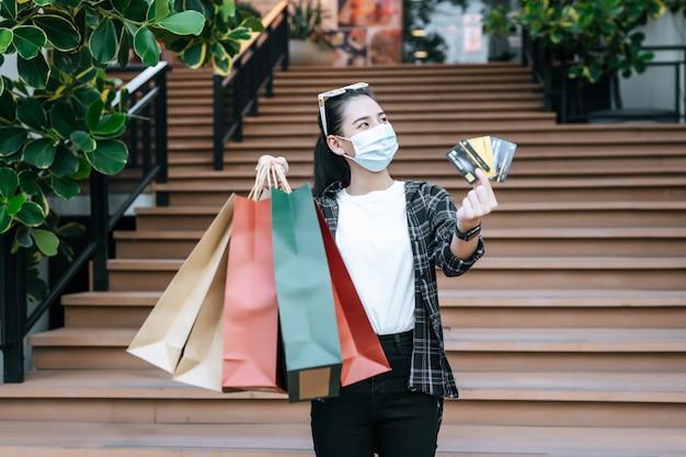Portret van een jonge aziatische vrouw met een beschermingsmasker, een bril op het hoofd die staat met een papieren boodschappentas