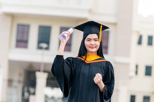 Portret van een jonge aziatische vrouw met een diploma in de buitenlucht