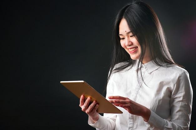 Portret van een jonge aziatische vrouw met een tablet op een zwarte achtergrond