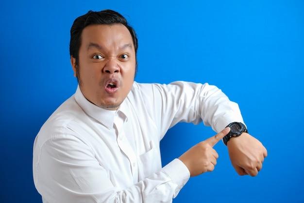Portret van een jonge aziatische zakenman die op zijn polshorloge wijst, baas die waarschuwt voor tijdconcept