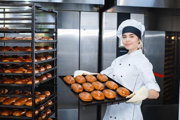 Portret van een jonge bakkersvrouw met industriële oven met gebakjes in een bakkerij
