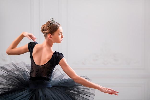 Portret van een jonge ballerina in een zwarte tutu, uitzicht vanaf de achterkant