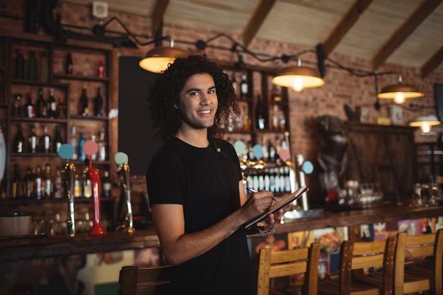 Portret van een jonge barman die op dagboek schrijft