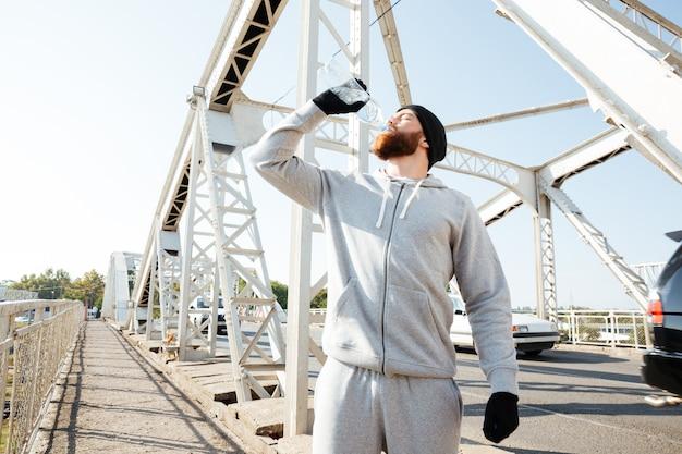 Portret van een jonge, bebaarde atleet in sportkleding die water drinkt terwijl hij bij de brug staat