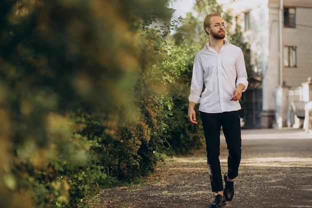 Portret van een jonge, bebaarde man die een bril draagt en in het park loopt