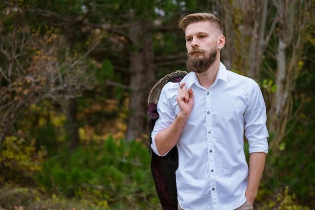 Portret van een jonge, bebaarde man die in de herfst op de weg in het park loopt, een knappe blanke man in