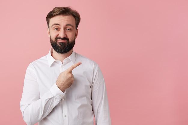 Portret van een jonge, bebaarde man, die met walging kijkt, vestig uw aandacht door met de vinger te wijzen op de kopie ruimte aan de rechterkant, geïsoleerd op een roze achtergrond.