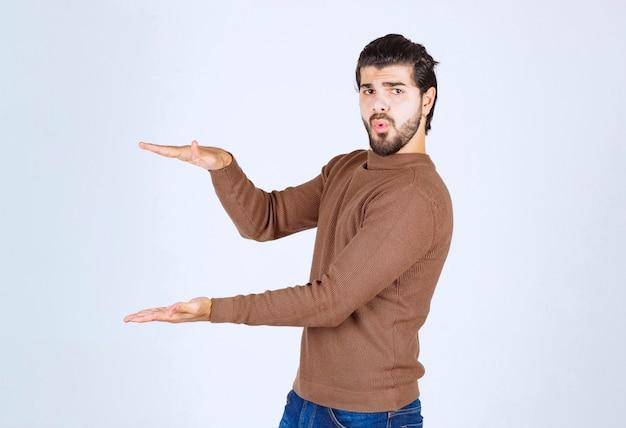 Portret van een jonge, bebaarde man die opschept over de grote omvang van iets.