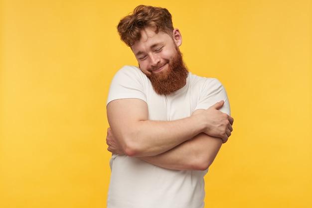 Portret van een jonge bebaarde man, draagt een leeg t-shirt, houdt zijn ogen dicht, knuffelt zichzelf en glimlacht op geel