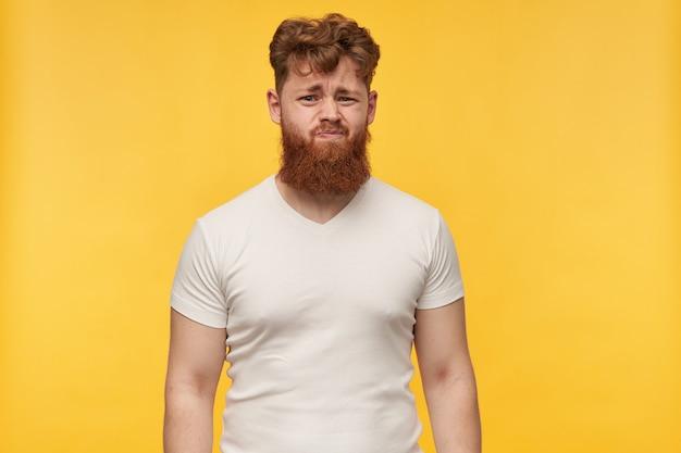 Portret van een jonge bebaarde man draagt een leeg t-shirt met walging gezichtsuitdrukking