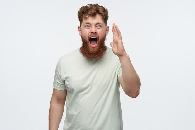 Portret van een jonge, bebaarde man, draagt een leeg t-shirt, schreeuwt met wijd geopende mond, voelt zich boos, boos op wit.