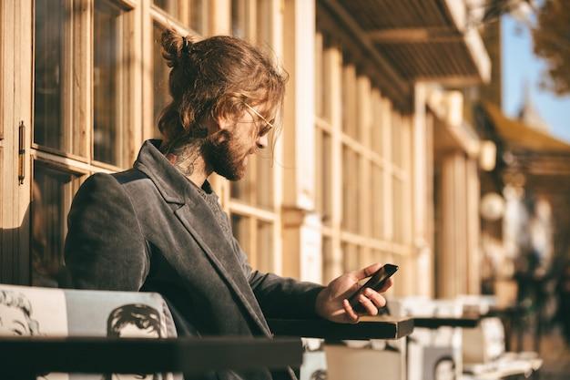 Portret van een jonge, bebaarde man gekleed in jas