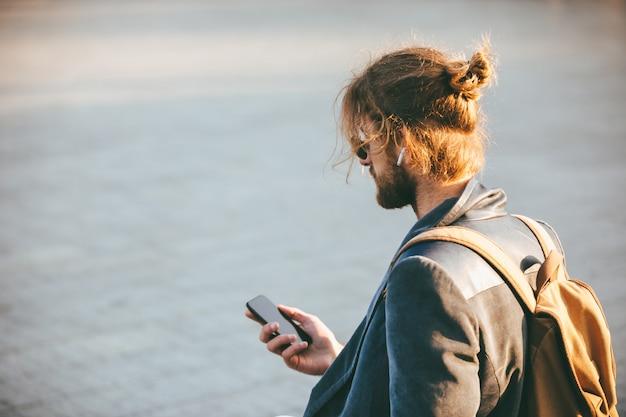 Portret van een jonge, bebaarde man in oortelefoons