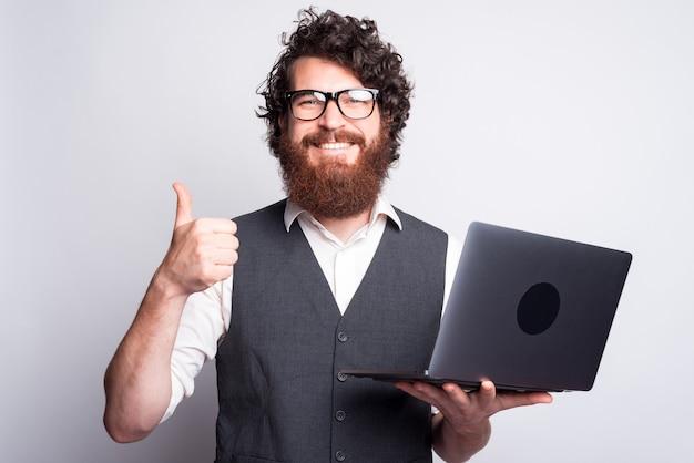 Portret van een jonge bebaarde man in pak duim opdagen en laptop te houden