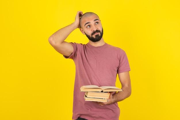 Portret van een jonge, bebaarde man met boeken over gele muur.