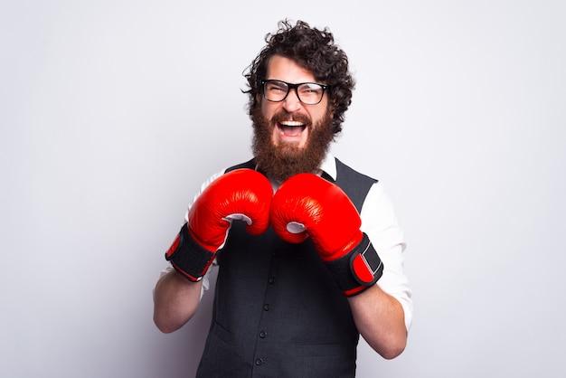 Portret van een jonge bebaarde man met pak schreeuwen en boksen met bokshandschoenen