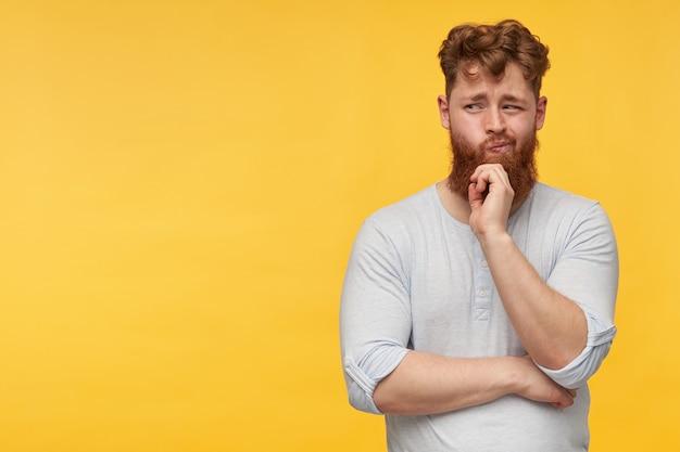 Portret van een jonge, bebaarde man met rood haar, draagt een leeg t-shirt, kijkt bedachtzaam opzij naar de kopie ruimte en trekt zijn kin op geel.