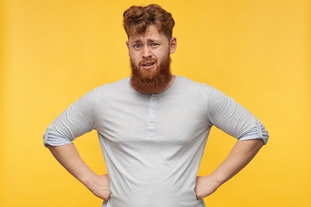 Portret van een jonge, bebaarde man met rood haar, houdt zijn handen op de heupen, voelt zich verward en ontevreden over geïrriteerde gezichtsuitdrukking op geel.